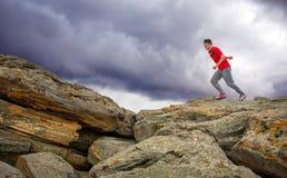 Sportman lopen, die over rotsen op berggebied springen Stock Foto