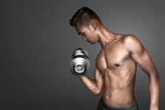 Sportman. Man doing exercise on grey background Stock Photography
