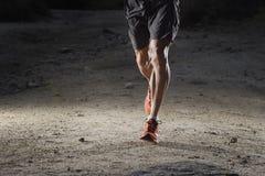 Sportman med rev sönder idrotts- och muskulösa ben som kör av vägen i jogga utbildningsgenomkörare på bygd i höstbakgrund royaltyfri fotografi