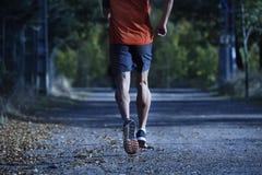 Sportman med rev sönder idrotts- och muskulösa ben som kör av vägen i jogga utbildningsgenomkörare på bygd i höstbakgrund arkivfoto