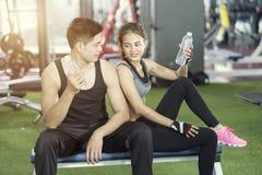 Sportman och kvinnadricksvatten efter genomkörare i idrottshallen royaltyfri fotografi