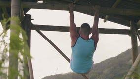 Sportman som hänger på utomhus- trämuskler för tvärslåutbildningsabs Manlig absgenomkörare på horisontalstång Tillbaka siktsidrot arkivfilmer