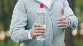 Sportman som visar tummarsom rymmer flaskan med drycken, dagligt vattenintag stock video