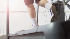Sportmanbenen die op tredmolenmachine lopen in gymnastiek, georiënteerd doel, duurzaamheid stock videobeelden