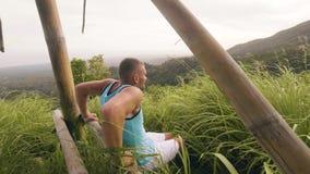 Sportmann, der oben Übung des Stoßes für den Trizeps ausbildet auf der hölzernen Stange im Freien tut Athletenmanntraining drückt stock video