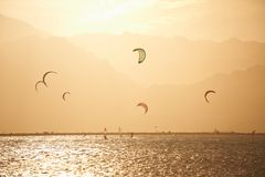 Sportmans kitesurfing on the sea surface against mountains at sunset time Stock Image