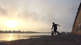 Sportmanstormlopen op Riverbank met Concrete Plakken bij Zonsondergang in slo-Mo stock videobeelden
