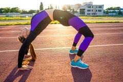 Sportmeisje belast met een opwarming bij het stadion bij zonsondergang royalty-vrije stock afbeelding