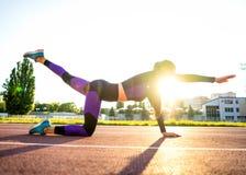 Sportmeisje belast met een opwarming bij het stadion bij zonsondergang stock foto's