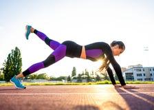 Sportmeisje bezette yoga in een opwarming bij het stadion bij zonsondergang stock foto's