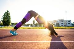 Sportmeisje bezette yoga in een opwarming bij het stadion bij zonsondergang royalty-vrije stock foto