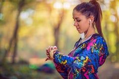 Sportmeisje die Dragend Smartwatch en Draadloze Oortelefoons lopen stock foto