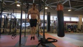 Sportmens de oefening van de opleidingstraining op gymnastiek- ringen in fitness club stock foto