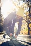 Sportmens in pauze van looppas bindende schoenveters stock foto's
