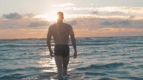Sportmodel bij zonsondergang op strand Geschikte mannelijke modelbuitenkant in zonsonderganglicht stock video