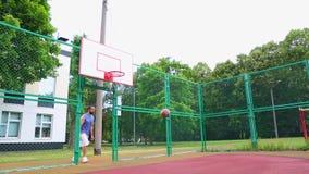 Sportmotivatie Het basketbal van de straat De speler noteert de bal in de mand op het straathof Opleidingsspel van stock videobeelden