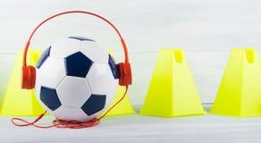 Sportmusik för sportar, fotbollboll med hörlurar, mot bakgrunden av gula trianglar Arkivbild