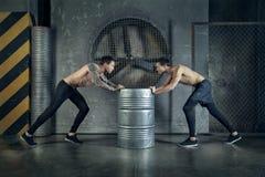 Sportowów faceci są pracujący z kruszcową baryłką out Zdjęcie Stock