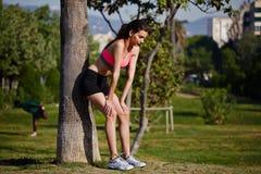 Sportowa atrakcyjna kobieta opierał z powrotem przeciw drzewu męczącemu po jogging Fotografia Royalty Free