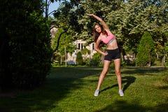Sportowa atrakcyjna kobieta robi rozciągania ćwiczeniu w pięknym zieleń parku Obraz Stock