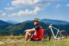 Sportowa cyklista w fachowym sportswear i hełma obsiadaniu blisko jego bicyklu na trawiastym poboczu zdjęcia royalty free