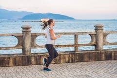 Sportowa dziewczyna na nadbrzeżu Młoda sportsmenka robi ćwiczeniom przeciw morzu zdjęcia stock
