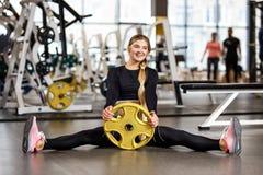 Sportowa dziewczyna z długim blondynem ubierającym w sportswear siedzi na podłodze z talerzem w nowożytnym gym zdjęcia royalty free
