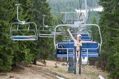 Sportowa dziewczyny narciarka ma zabawę na narciarskim dźwignięciu, jazdie do wierzchołka i seans aprobaty z nartami i góra Obrazy Royalty Free