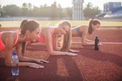 Sportowa grupa kobiety trenuje na słonecznym dniu robi zaszalujący ćwiczenie w stadium Zdjęcie Stock