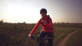 Sportowa Kaukaska kobieta je proteina baru przeja?d?k? na rowerze g?rskim na naturze M?oda sporty kobiety atleta w he?ma odpoczyw zdjęcie wideo