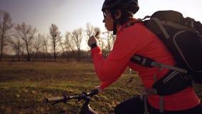 Sportowa Kaukaska kobieta je proteina baru przeja?d?k? na rowerze g?rskim na naturze M?oda sporty kobiety atleta odpoczywa w he?m zdjęcia stock
