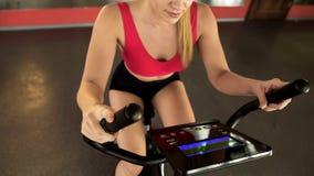 Sportowa kobieta jedzie stacjonarnego rower i patrzeje elektronicznego panel, sport fotografia stock