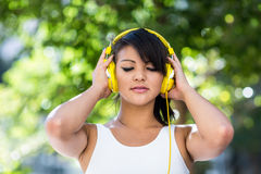 Sportowa kobieta jest ubranym żółtych hełmofony i cieszy się muzykę z oczami zamykającymi Zdjęcia Stock