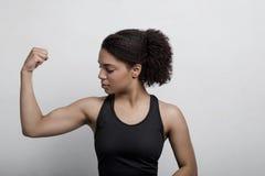 Sportowa kobieta napina jej ręka mięsień Zdjęcie Stock