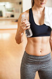 Sportowa kobieta pije niektóre wodnych z abs fotografia royalty free