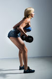 Sportowa kobieta pompuje up muscules z dumbbells zdjęcia stock