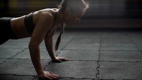 Sportowa kobieta robi Ups na podłogowym zakończeniu w w górę zwolnionego tempa w gym zbiory