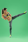 Sportowa kobieta trenuje jej wysokiego kopie wewnątrz studio na zielonym backgro obraz royalty free