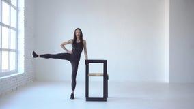 Sportowa kobieta w sportswear wykonuje bocznych kopnięcia z pomocą krzesła w białym studiu 4k materiał filmowy zbiory