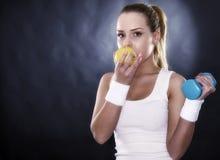 Sportowa kobieta wręcza dojrzałego żółtego jabłka Zdjęcie Royalty Free