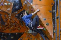 Sportowa kobieta wspina się indoors, widok od plecy Obraz Stock