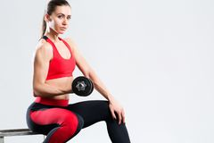 Sportowa kobieta z dumbbells robi sporta ćwiczeniu, odosobnionemu na szarym tle zdjęcie stock