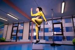 Sportowa młoda kobieta używa krok platformę w gym obrazy royalty free