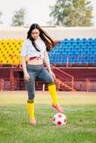 Sportowa młoda seksowna dziewczyna na boisku piłkarskim z piłką na pogodnym letnim dniu zdjęcie stock