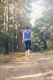 Sportowa młoda kobieta jogging wzdłuż lasowego śladu Zdjęcia Royalty Free