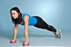 Sportowa młoda kobieta robi rozciągań ćwiczeniom zdjęcie royalty free