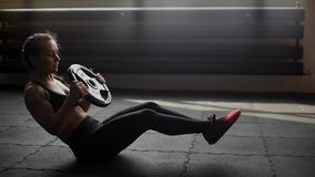 Sportowa mięśniowa kobieta trenuje abs, robi przekręcać w zwolnionym tempie w gym zbiory wideo