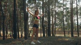 Sportowa nikła dziewczyna w jaskrawym upierzeniu robi treningowi zbiory wideo