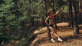 Sportowa piękna dziewczyna w krótkich skrótach i wierzchołków stojakach blisko drzewa i robi fotografii zdjęcie wideo