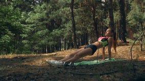 Sportowa sprawności fizycznej dziewczyna w jaskrawych upierzenie stojakach w lath na rękach zdjęcie wideo